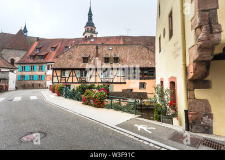 street of the village Andlau, Alsace Wine Route, France, half-timbered houses and ancient monastery with church in the background - Stock Photo