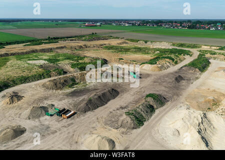 Soil heaps and material for soil recycling at the edge of a sand pit in Germany, taken from the air with the drone. - Stock Photo