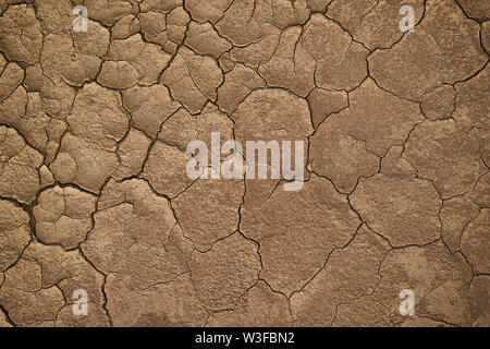Dry cracked earth during in a rainy season because lack of rain shortage of water cracked soil texture - Stock Photo