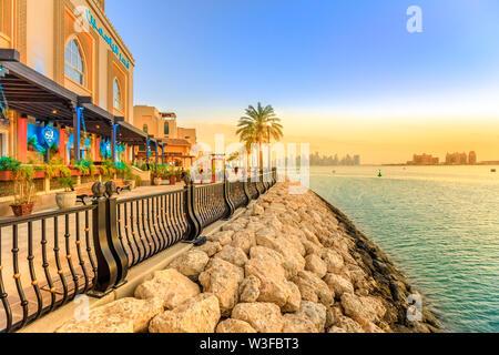 Doha, Qatar - February 18, 2019: amazing sunset in marina walkway promenade in Porto Arabia, the Pearl, with the St. Regis Doha and Doha West Bay on - Stock Photo