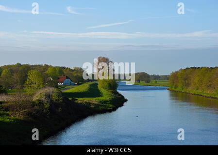 papenburg, niedersachsen/germany - may 04, 2015: ems river meandering near herbrum and a farm house at its banks - Stock Photo