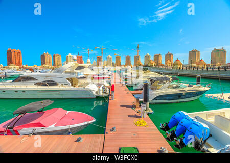 Doha, Qatar - February 18, 2019: Marina corniche promenade with luxury boats and yachts in Porto Arabia at the Pearl-Qatar. Residential towers on - Stock Photo