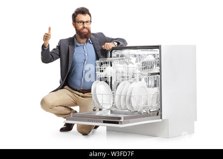 Man kneeling next to a dish washing machine and showing thumbs up isolated on white background