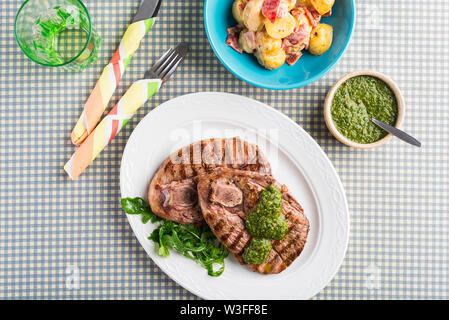 Chargrilled British Lamb leg steaks with chimichurri sauce and potato salad, overhead on chequered table cloth - Stock Photo