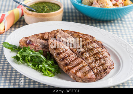 Chargrilled British Lamb leg steaks with chimichurri sauce and potato salad on chequered table cloth - Stock Photo