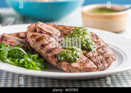 Chargrilled British Lamb leg steaks with chimichurri sauce and potato salad. Close up with the sauce. - Stock Photo