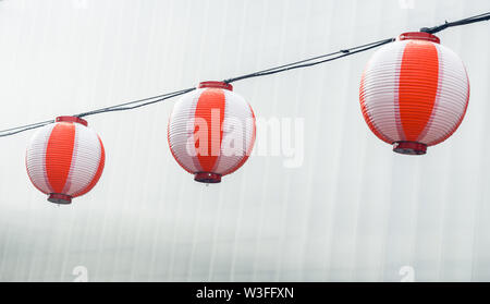 Three round paper red-white japanese lanterns Chochin hanging on garland sky background - Stock Photo
