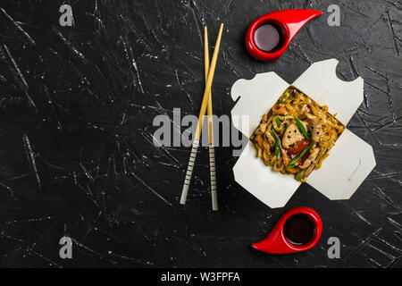 Chinese noodles in a box with chicken and vegetables with sticks. Wok food delivery from restaurant on dark background from top view. - Stock Photo
