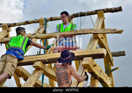 Building a traditional Anglo Saxon style heavy oak framed hall building using traditional methods lifting a beam up with ropes and manual handling - Stock Photo