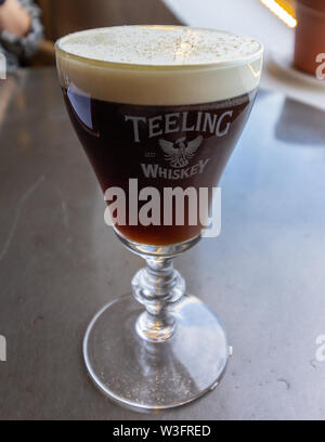 Dublin, Ireland - January 20, 2019 - In the Teeling Distillery tasting room whiskey based cocktails can be purchased. Pictured is an Irish coffee in l - Stock Photo