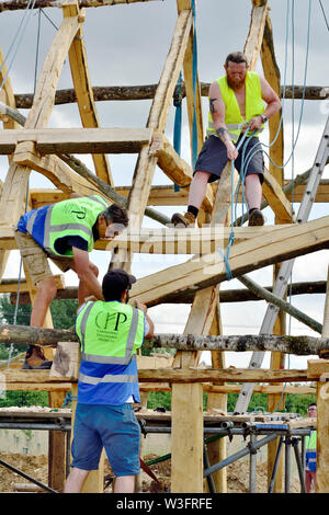 Building a traditional Anglo Saxon style heavy oak framed hall building lifting a beam up with ropes and manual handling - Stock Photo