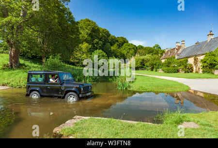 Land Rover Defender crossing the river Eye at a fording point. Upper Slaughter, Cotswolds,  Gloucestershire, England, UK. - Stock Photo