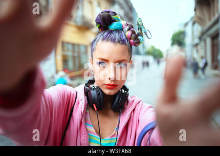 Cool funky young hipster woman with trendy avant garde look taking selfie on London street - Stock Photo