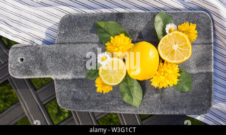 A selection of lemon slices arranged on a grey slate chopping board with leaves and floral accents. - Stock Photo