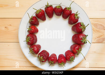 Red ripened strawberries laid out in circle shape on white plate on light wooden table. Copy space in center of frame. Place for text. Delicious natur