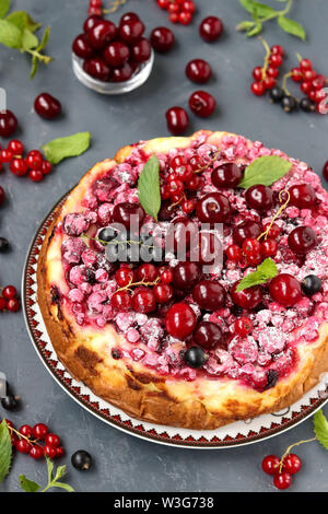Summer cottage cheese cake with berries is located on a dark background, vertical photo, close-up, top view - Stock Photo