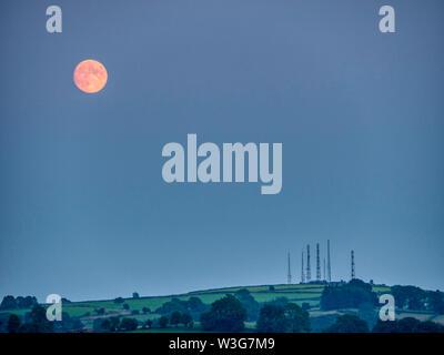 UK Weather: spectacular orange full Buck moon over Alport Heights, Wirksworth Derbyshire UK - Stock Photo