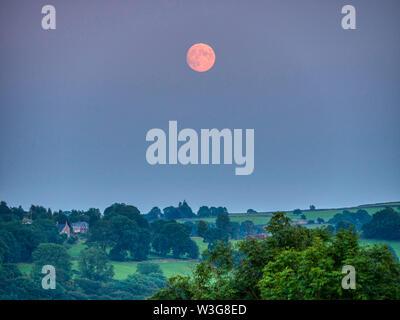 UK Weather: spectacular orange full Buck moon over  Wirksworth Derbyshire UK - Stock Photo