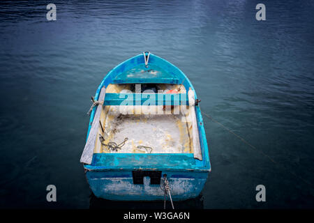 Small blue wooden rowing fisherman boat in the port and harbour in the Alykes Bay in Zante, Greece - Stock Photo