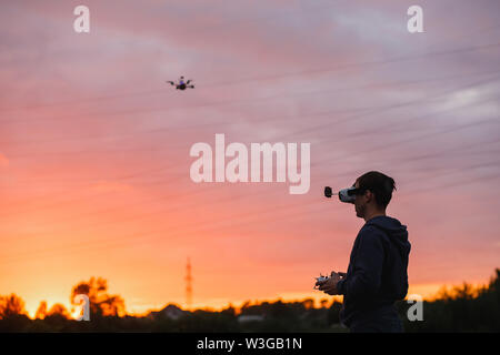 Man controlling custom made dron by virtual reality glasses near power lines on sunset. - Stock Photo
