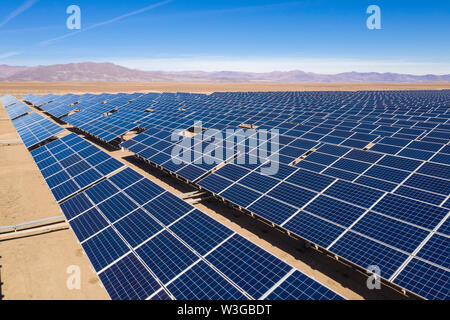 Aerial view of hundreds solar energy modules or panels rows along the dry lands at Atacama Desert, Chile. Huge Photovoltaic PV Plant in the desert
