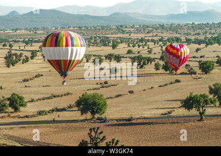Colorful hot air balloons landing in rural farm fields - Stock Photo