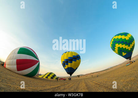Teotihuacan, Mexico - April 6, 2019 : Colorful hot air balloons about to take off at dawn in rural field with blue sky near the town of Teotihuacan, M - Stock Photo