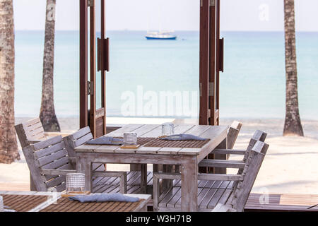 Tropical beach cafe with wooden table and chairs with blue sea water on background, Thailand. Rustic wooden furniture on a balcony overlooking a beaut - Stock Photo
