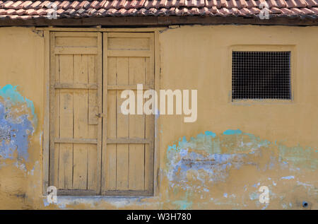 Old  clay tiled roofing Kerala style house with vibrant yellow paint and rustic antique look taken in rural India. - Stock Photo