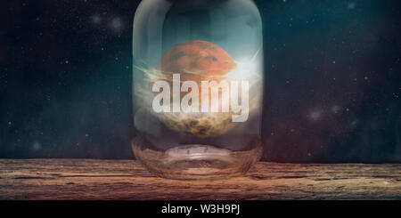 Mars in glass bottle on a wooden table infinity space background. - Stock Photo