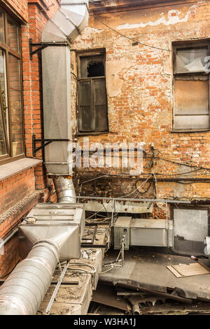 Metal air duct from the kitchen of the restaurant , laid on a brick wall . The courtyard of the old house . Site about  architecture , kitchen . - Stock Photo