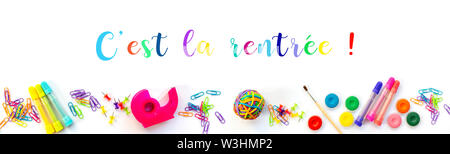 Panorama of colorful school supplies  on white background with with text 'c'est la rentree' meaning Back to School in French - Stock Photo