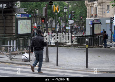 man crossing street under red traffic lights at metro station Barbes Rochechouart, Paris, France - Stock Photo