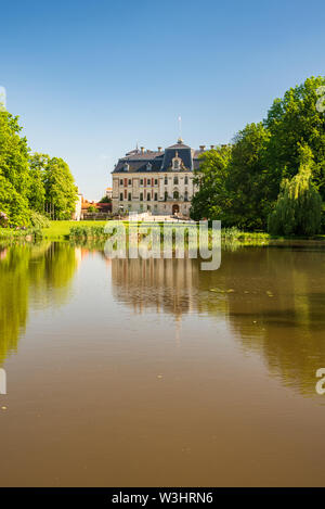 Pszczyna chateau mirroring in small lake water ground with trees around in Poland during beautiful springtime day with clear sky - Stock Photo