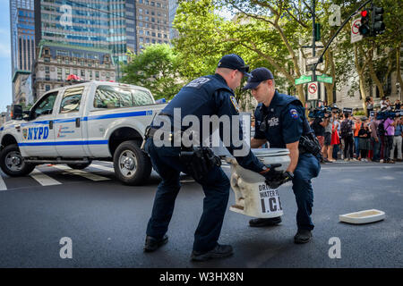 "A dirty toilet bowl was placed to call attention to the migrants forced to drink from it - More than 40 members of the direct action group Rise and Resist were arrested after shutting down rush hour traffic at the intersection of 42nd Street and Fifth Avenue in the heart of New York City on July 15, 2019 advocating for immigrants' rights and demanding the public wake up, take action, and end the border crisis terror and the terror inflicted on immigrant communities. Activists held three banners that read, ""Close the Camps"", ""No Raids"", and ""Abolish ICE"". Some members also wore fluorescent work - Stock Photo"