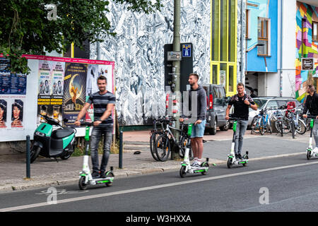 Tourists on e-scooters; In Friedrichshain-Berlin. The electric scooter is the latest form of transport in Germany.; E-scooters have recently been made legal for street use in Germany and are making an appearance in Berlin. Use is restricted to bike lanes & streets. The maximun speed allowed is 20kpm and under- fourteens are not permitted to use the scooters. - Stock Photo