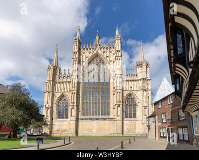 The East end of York Minster with the medieval Great East Window.  A row of houses is to one side and a blue sky with clouds is above. - Stock Photo