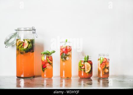Homemade strawberry and basil lemonade or ice tea in glass tumblers with eco-friendly plastic-free straws on grey concrete table, white wall at backgr - Stock Photo