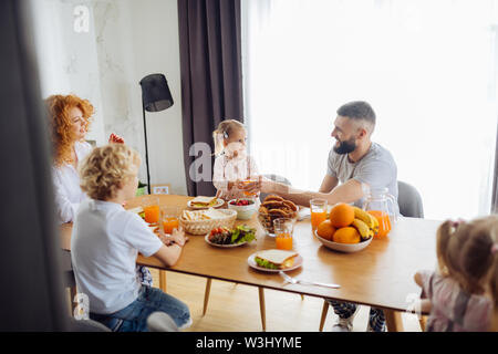 Caring dad. Pleasant nice man looking at his daughter while giving a glass of juice to her - Stock Photo