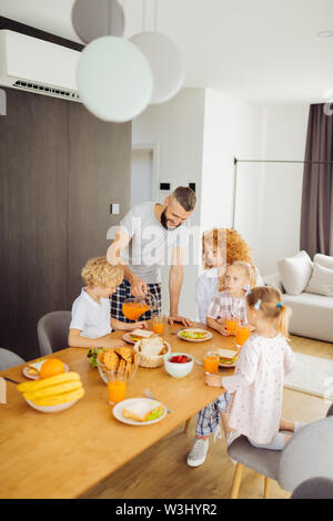 Love and care. Pleasant nice man pouring juice into glasses while taking care of his family - Stock Photo