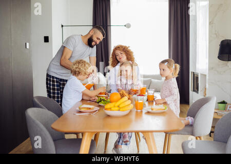 Refreshing drink. Nice pleasant family looking at the father while waiting for the juice to be served - Stock Photo