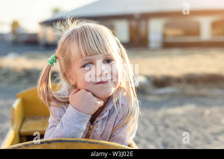 Adorable cute caucasian blond kid girl portrait sitting in wooden cart, looking aside and dreaming at farm or park during warm autumn evening
