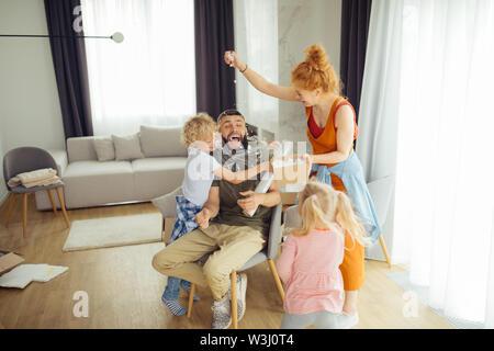 Love to fun. Joyful nice family having fun while playing games together - Stock Photo