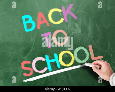 hand holding piece of chalk against colorful words BACK TO SCHOOL written on chalkboard - Stock Photo