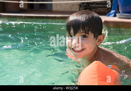 Boy wearing arm floats in a swimming pool - Stock Photo