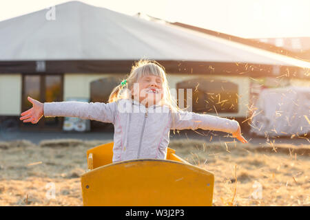 Adorable cute caucasian blond kid girl sitting in wooden cart having fun throwing straw or hay at farm or park during warm autumn evening. Happy - Stock Photo