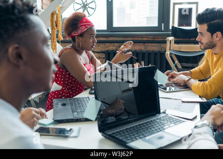 A team of young people of different nationalities discusses the work on the project in the office. - Stock Photo