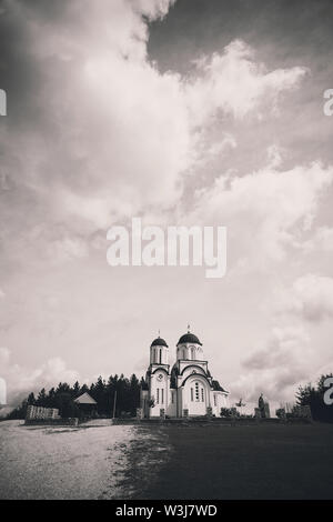 Exterior of a small Orthodox church on the hill in black and white. - Stock Photo