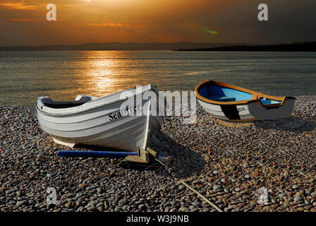 A photo montage of Boats and the Setting Sun over Budleigh Beach. - Stock Photo