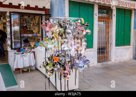 Display of traditional Venice carnival masks for sale outside a shop in the centre of Burano, a small island in Venice Lagoon, Venice, Italy - Stock Photo
